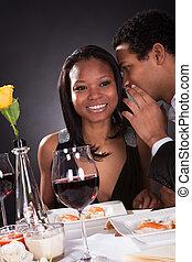 Man Whispering To Girlfriend's Ear
