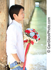 portrait of man with beautiful bouquet on the beach