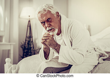 Portrait of man with black eye sitting on a bed
