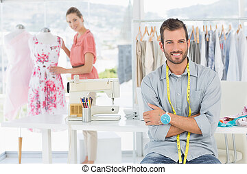 Portrait of man with female fashion designer working at studio