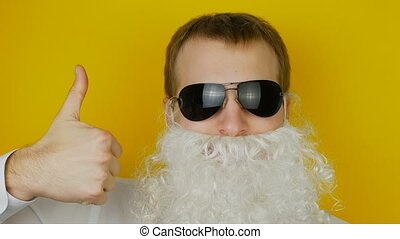 Portrait of man with white beard and black glasses, thumbs...