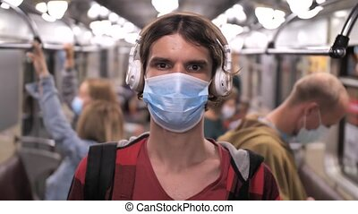 Close-up portrait of tall male in protective face mask and headphones looking at camera while riding in subway train, against background of blurred unrecognizable passengers wearing medical masks