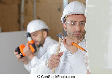 portrait of mason hammering the wall