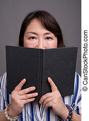 Portrait of mature beautiful Asian businesswoman reading book