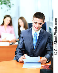 Portrait of mature business man smiling during meeting with colleagues in background