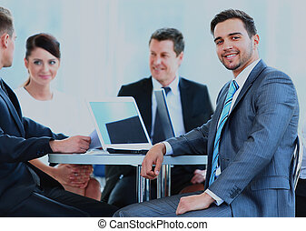 Portrait of mature business man smiling during meeting with colleagues in background.