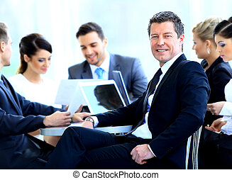 Portrait of mature business man smiling during meeting with...