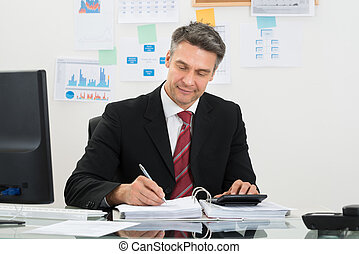 Portrait Of Mature Businessman Calculating Finance At Office Desk