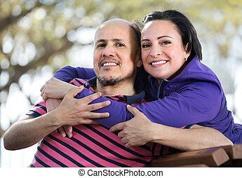 Portrait of cheerful mature couple hugging each other outdoors.