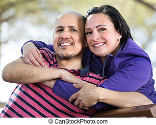 Portrait of romantic mature couple hugging each other outdoors.