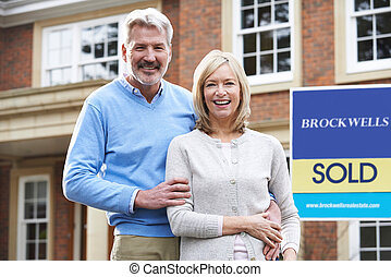 Portrait Of Mature Couple Outside New Home Standing By Sold Sign