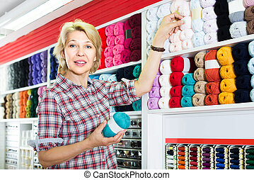 portrait of mature female customer standing next to shelf with knitting yarn in shop