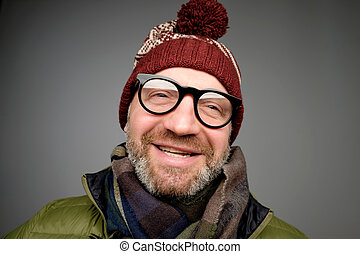 Portrait of mature hipster man in glasses and hat posing. Smiling bearded man wearing warm clothes for winter
