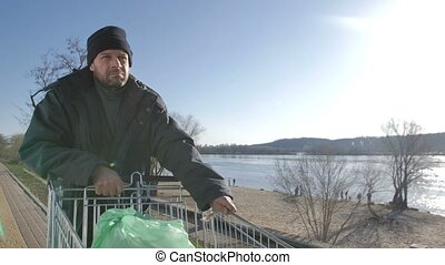 Portrait of mature homeless man walking near river -...