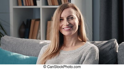 Portrait of mature lady sitting on couch and smiling