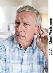 Portrait Of Mature Man Suffering From Deafness At Home