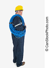 Portrait of mature repairman wearing hardhat with cable