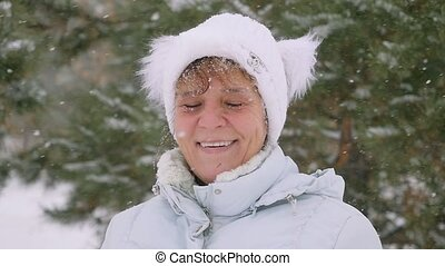 Portrait of mature smiles woman in aged stand in the park during snowfall in slowmotion. 1920x1080