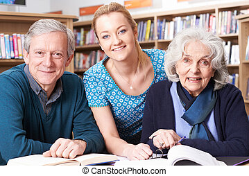 Portrait Of Mature Students Working With Teacher In Library