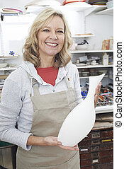Portrait Of Mature Woman Holding Vase In Pottery Studio