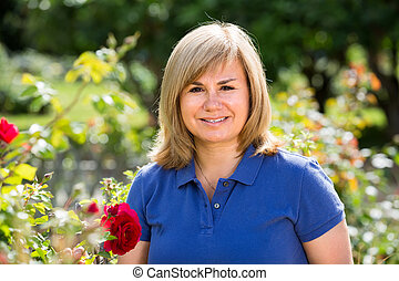 portrait of mature woman in garden on summer day.