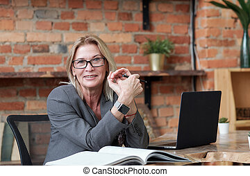Portrait of mature woman in loft office
