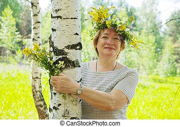 woman near birch in flowers wreath