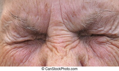 Portrait of mature woman screwing up her gray eyes and then...