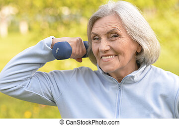 Portrait of mature woman with dumbbell in park