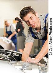 Portrait of mechanic repairing car