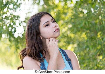 Portrait of melancholy teen girl on nature