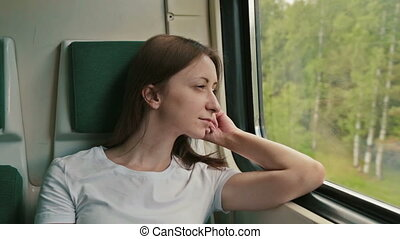 young woman looking out the window of a train - portrait of...