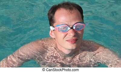 portrait of men with goggles in swimming pool with blue water