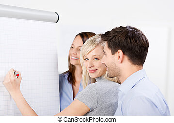 Portrait of mid adult businesswoman writing on presentation board with coworkers looking at it in office