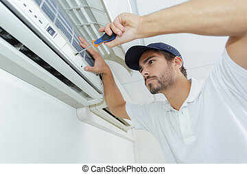 portrait of mid-adult male technician repairing air conditioner