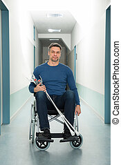 Man Sitting On Wheelchair With Crutches