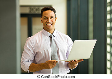 mid age employee holding laptop - portrait of mid age ...