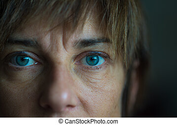 Portrait of mid aged woman with blue eyes, close up and selective focus on one eye, very shallow depth of field. Dark setting, toned image.