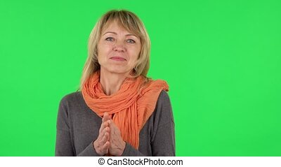 Portrait of middle aged blonde woman is waiting in anticipation with pleasure. Green screen