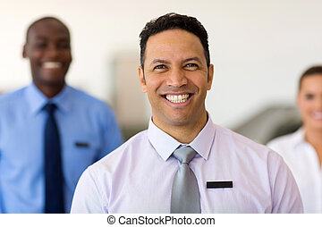 middle aged car dealership principal with staff