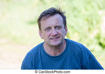 Portrait of middle-aged man relaxing in nature, close up -...