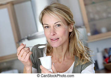 Portrait of middle-aged woman eating yogurt