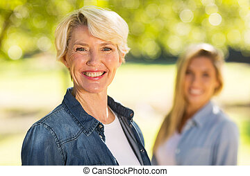 middle aged woman in front of young daughter