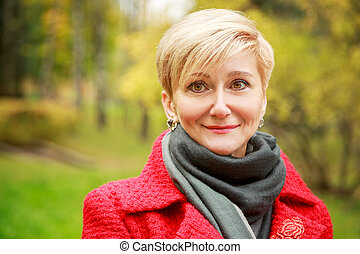 Portrait of Middle Aged Woman on Autumn Background