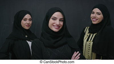 Group portrait of beautiful Muslim women in traditional middle eastern dress with hijab isolated on black chalkboard background
