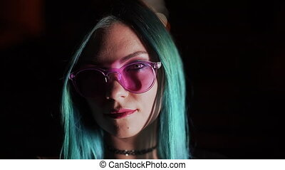 Portrait of millennial enigmatic pretty girl with unusual dyed blue hairstyle at night. Mysterious hipster woman in glasses. . High quality FullHD footage