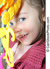 portrait of mischievous little girl posing with toy