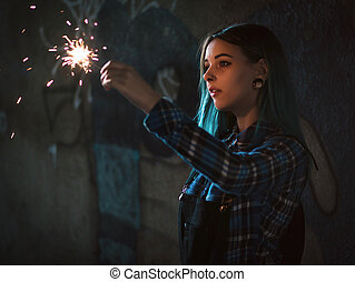 Portrait of model girl with blue hair looks with sparklers in their hands. Close up. Beautiful young teenage in city tunnel having fun with bengal fire.