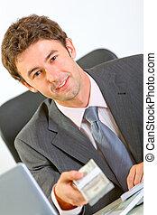 Portrait of modern businessman sitting at office desk giving dollars pack