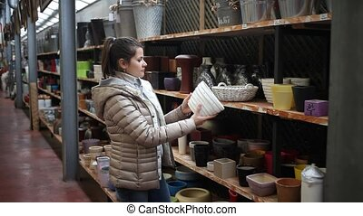 Young positive woman looking for flower pots in hypermarket. Concept of gardening and floriculture